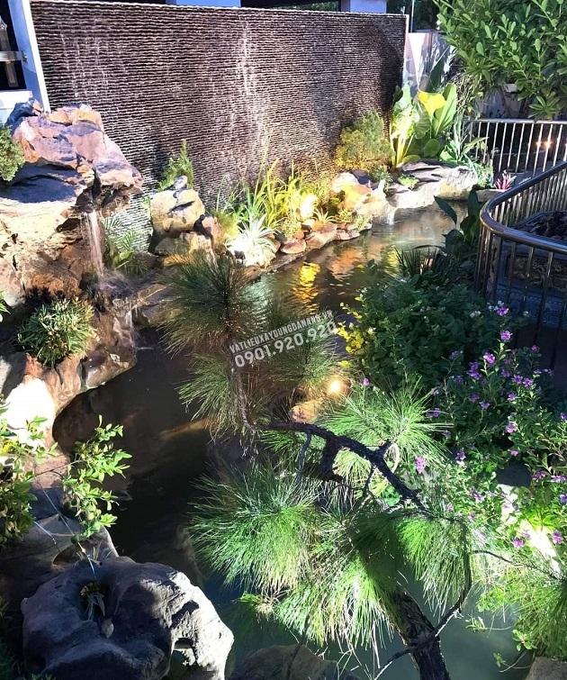 Một góc sân vườn với hồ cá Koi và tường đá suối đen tự do